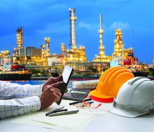 engineer working on computer tablet against beautiful oil refinery background