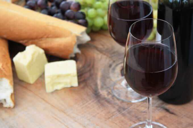 Wine, Bread, Cheese, Grapes on Outdoor Wooden Table