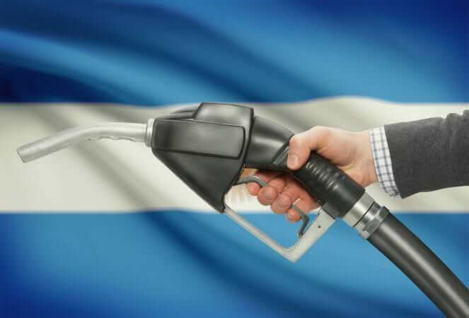 Fuel pump nozzle in hand with flag on background - Argentina