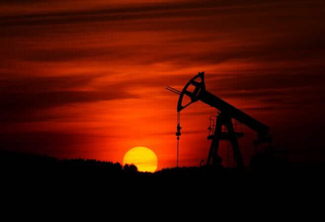 Oil Pump Jack against a red setting sun on horizon